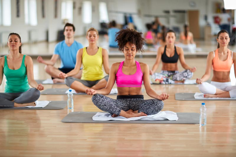 A group of women in an exercise studio doing yoga