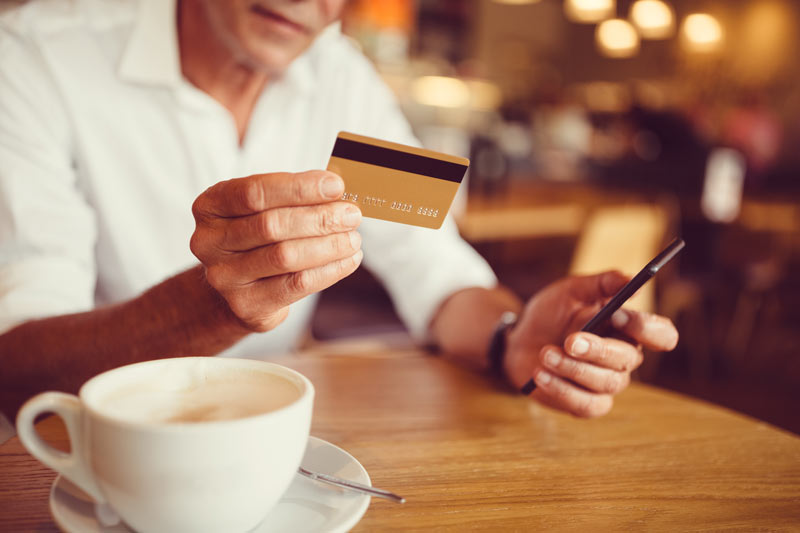 A man in a coffee shop holding his credit card while holding his phone