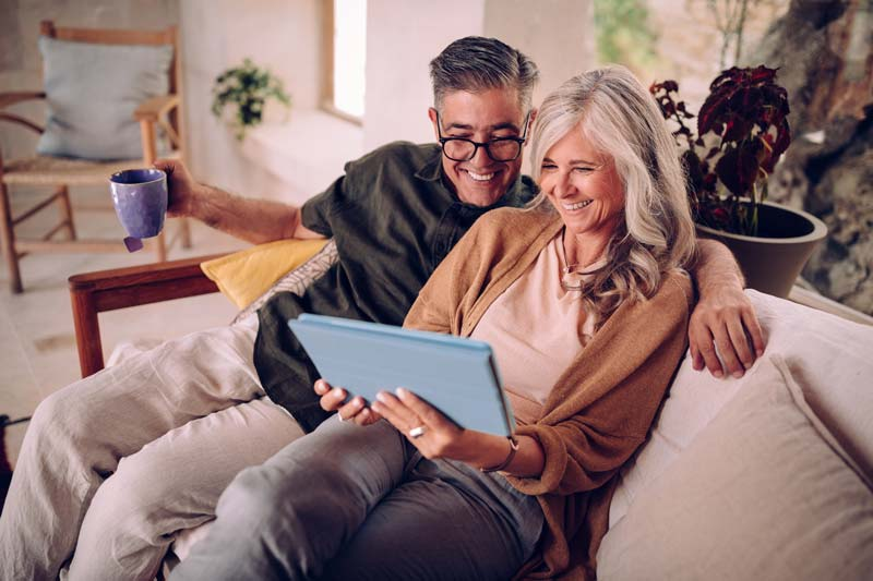 A mature couple sitting on a couch, smiling while looking at their tablet screen