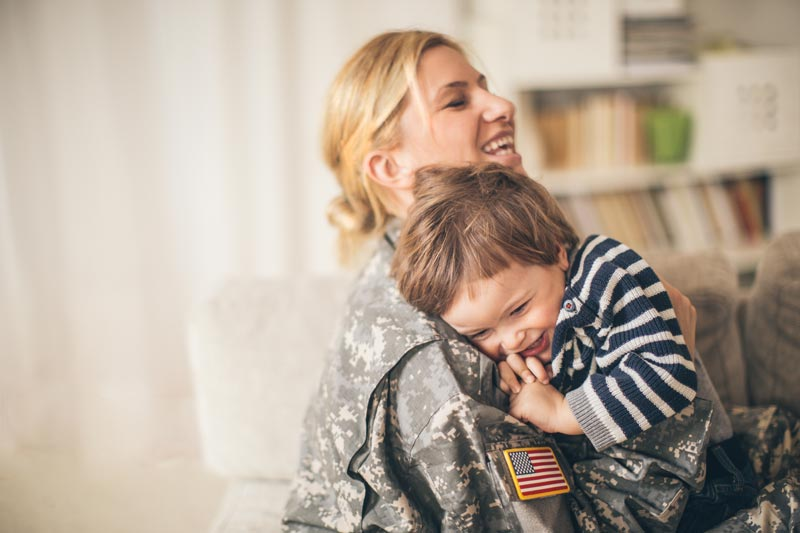 A military mom hugging her son