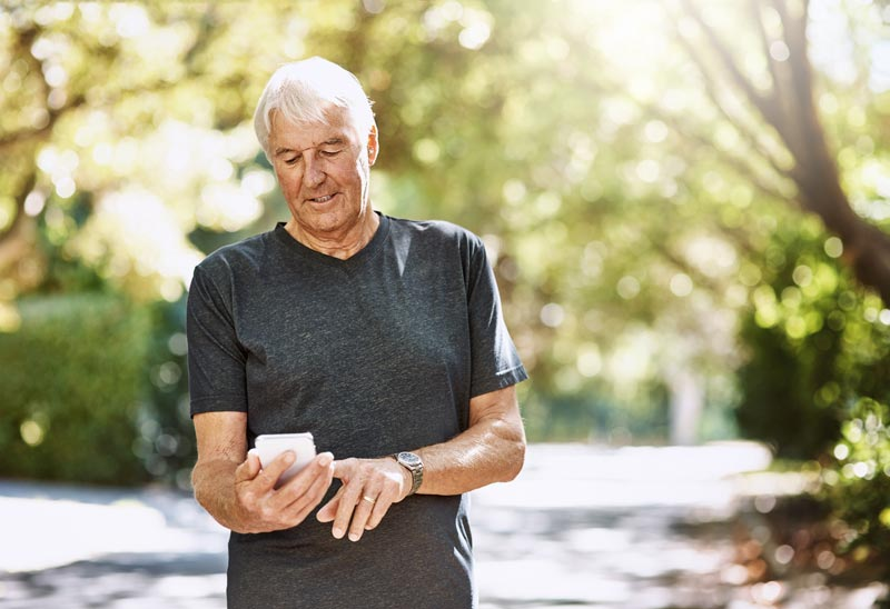 Older man outside exercising while looking at his smart phone