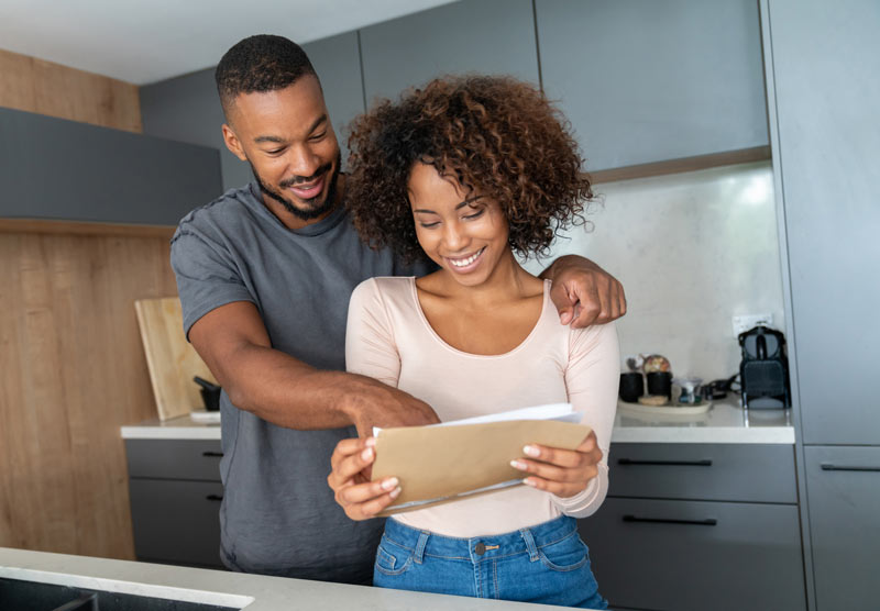 A young couple standing in the kitchen with arms around each other while looking at a tablet